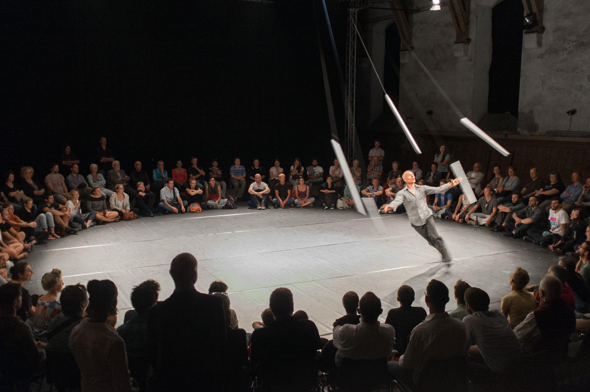 Ein Künstler jongliert in einer Manege