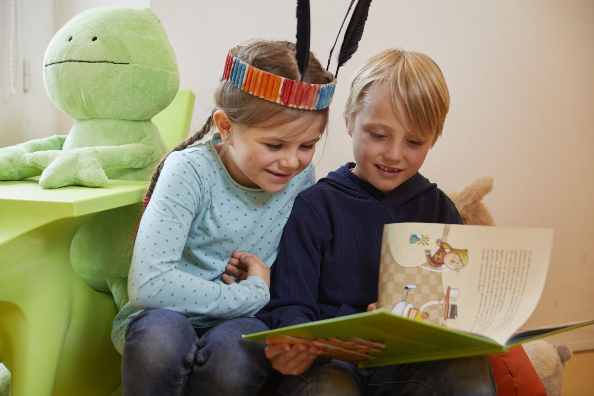 Zwei Kinder lesen gemeinsam in einem Buch