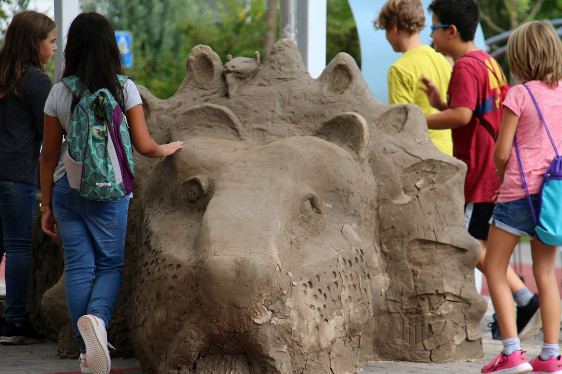 Kinder arbeiten an einem überlebensgrossen Löwen aus Lehm