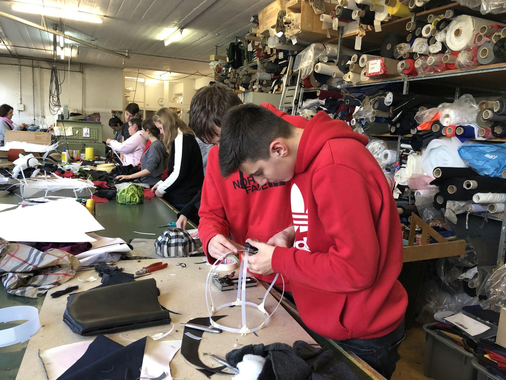 Schülerinnen und Schüler in einer Werkstatt mit vielen Stoffrollen im Hintergrund
