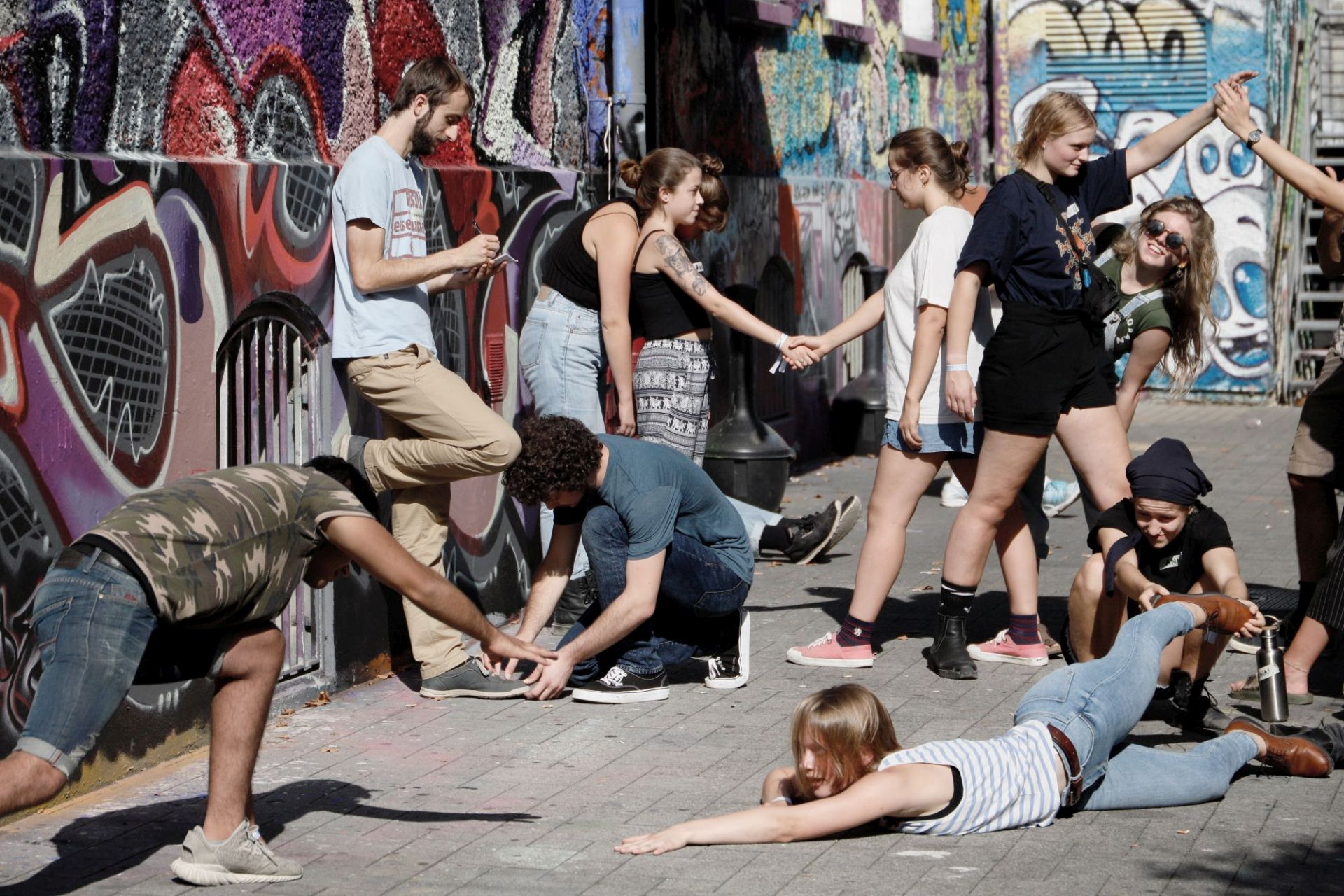 Jugendliche stehen und sitzen in unterschiedlichen Posen vor eine Graffiti-Wand