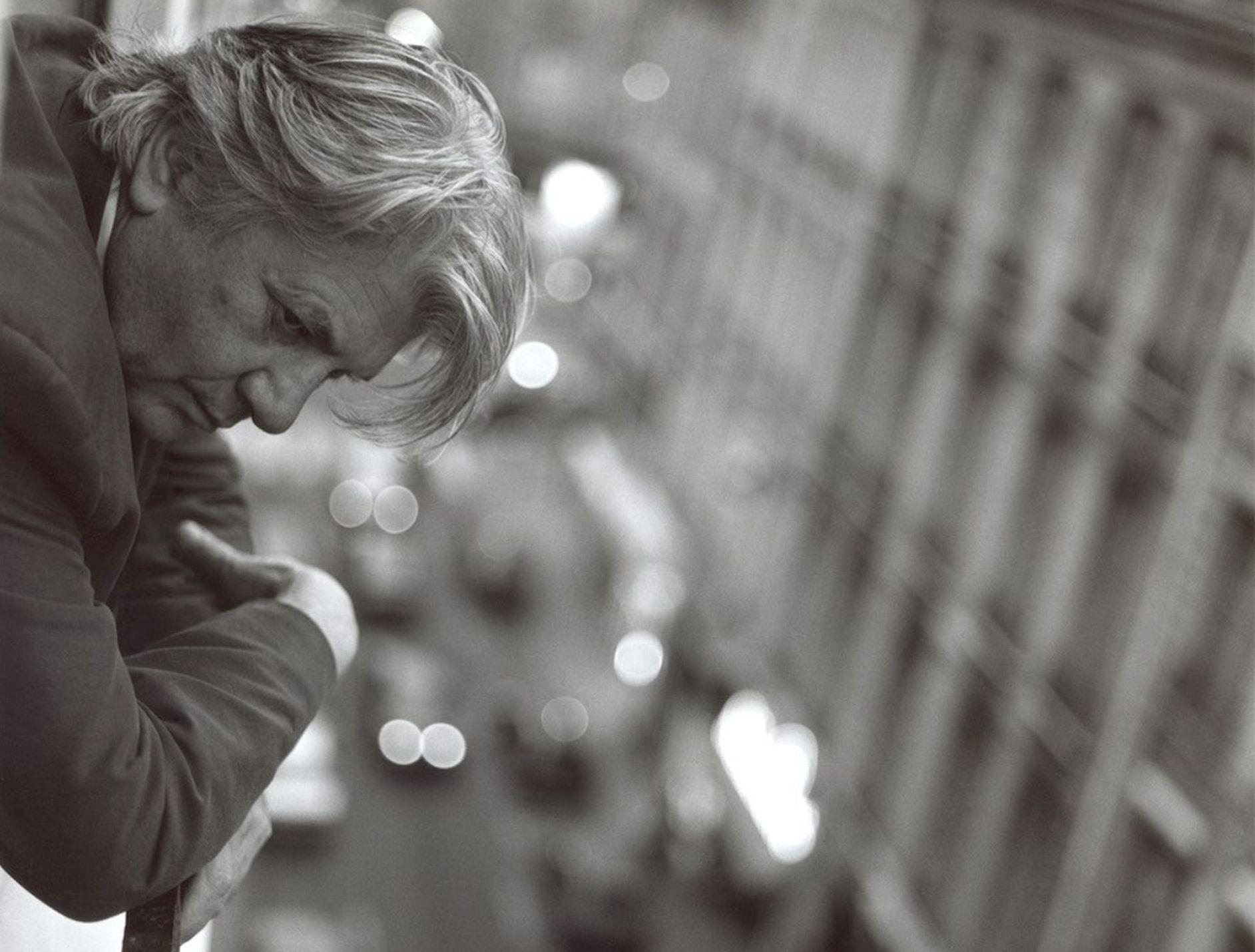 schwarz-weiss Foto eines Mannes, der aus dem Fenster auf die Srasse schaut