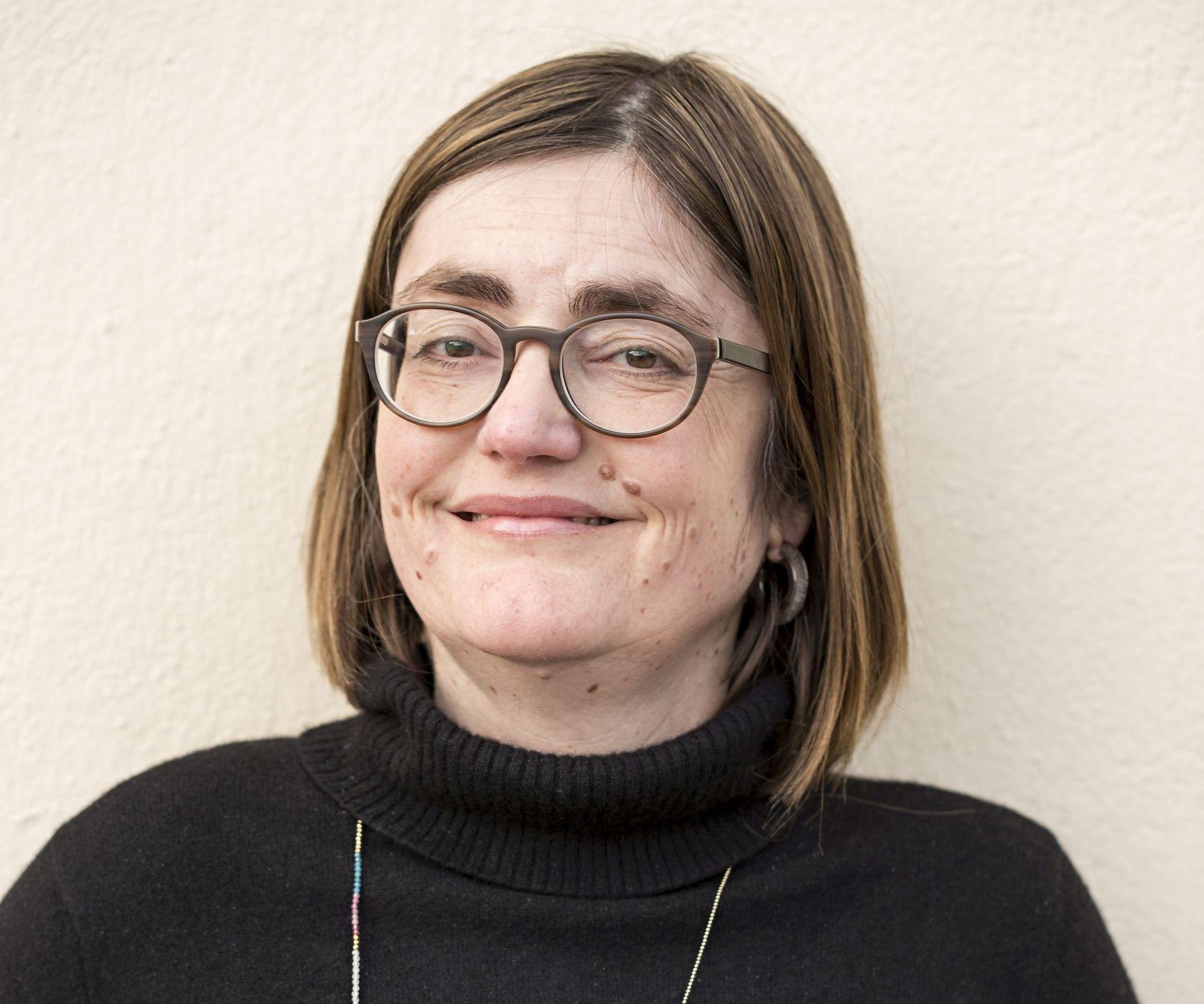 eine schwarz gekleidete Fau mit Brille