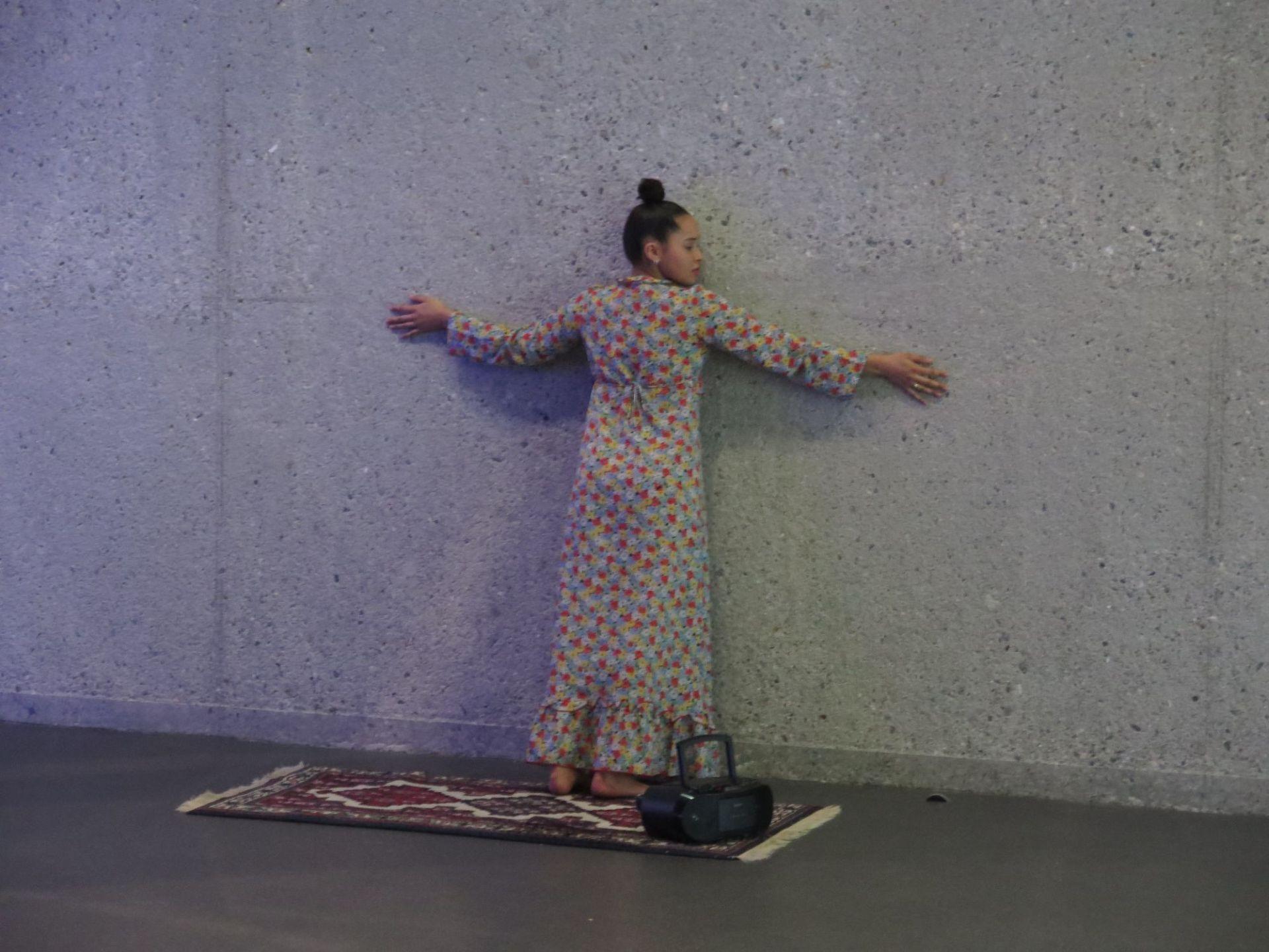 Ein junge Frau umarmt eine graue Wand