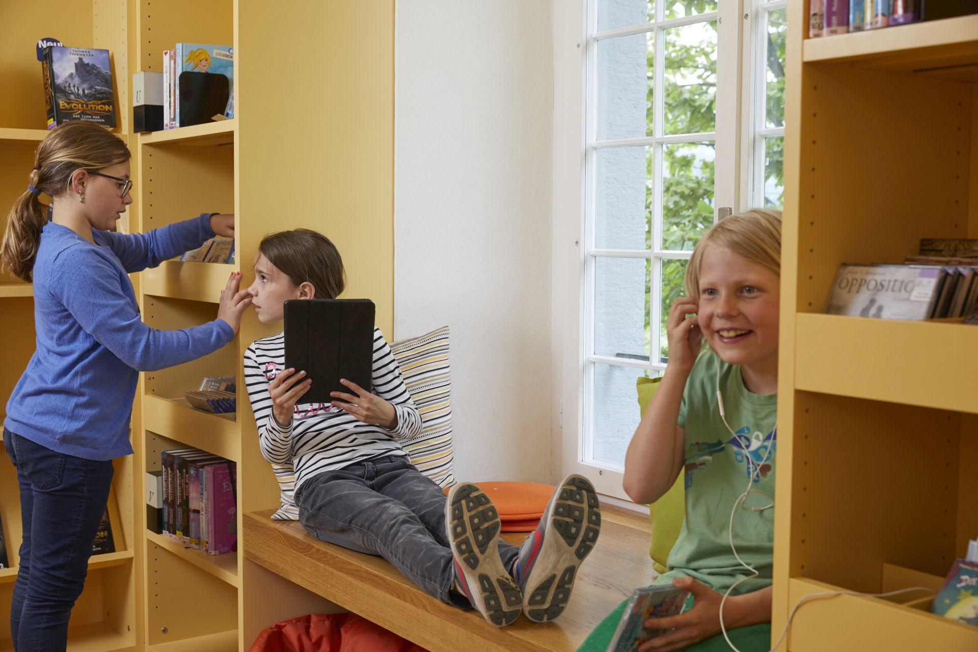 drei Mädchen vergnügt in einer Bibliothek