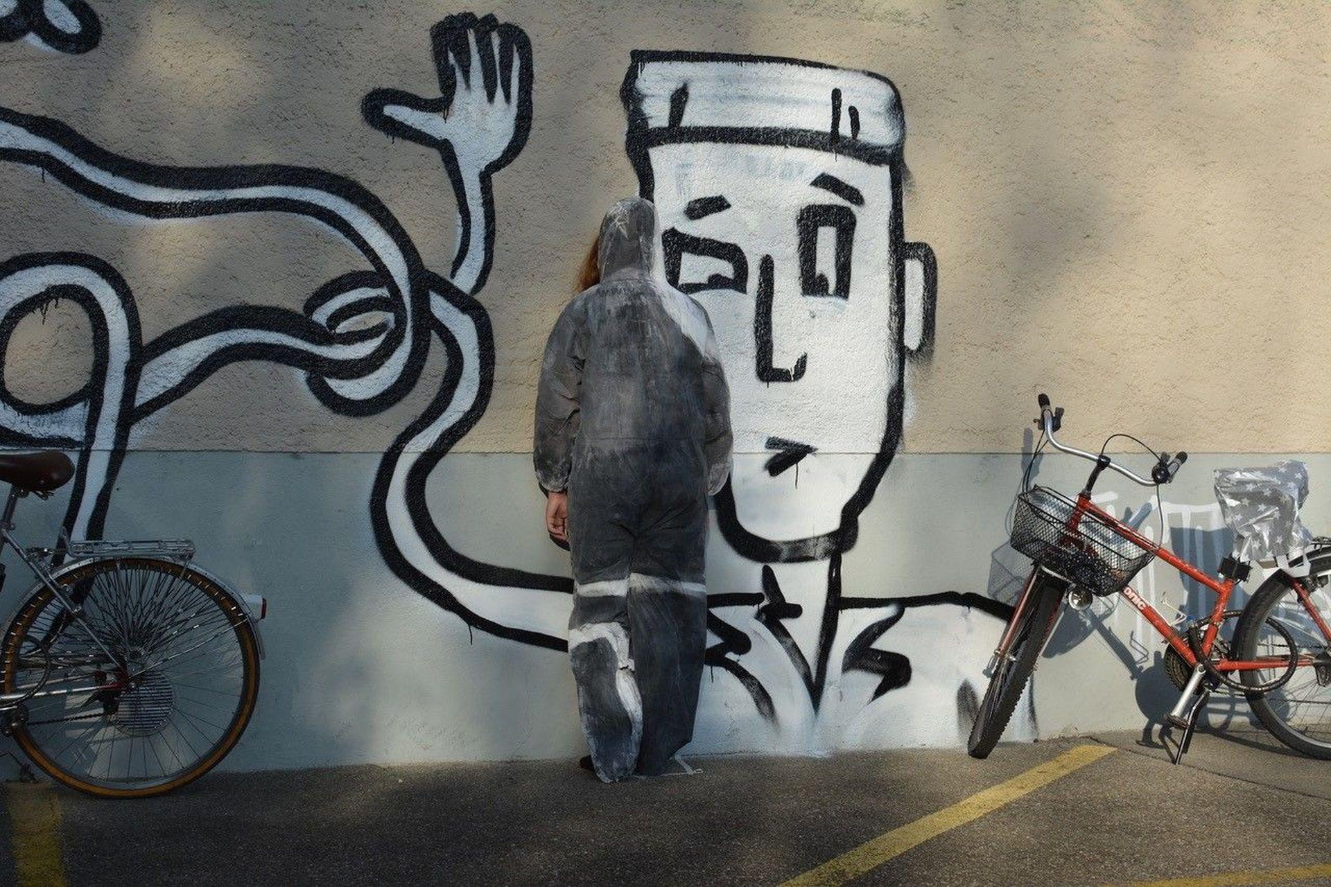 Person mit Kapuzenpullover vor gesprayter Comicfigur