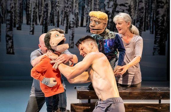 Schauspieler würgt eine menschengrosse Puppe, zweite Puppe schaut zu