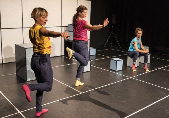 Zwei Tänzerinnen springend, eine sitzend, in bunten T-Shirts