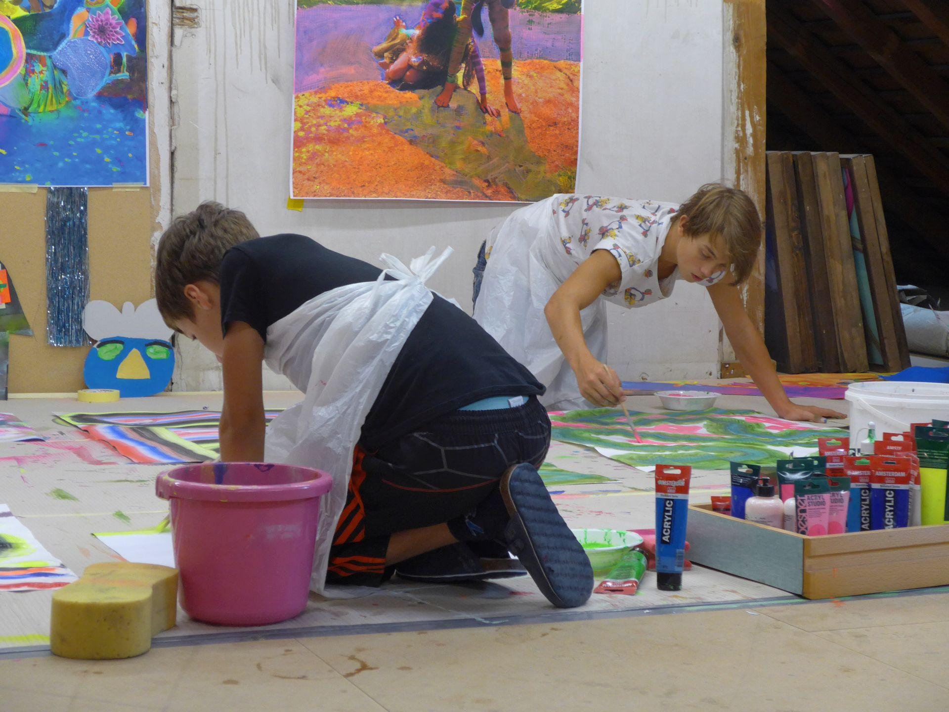 Zwei Buben knien am Boden und malen