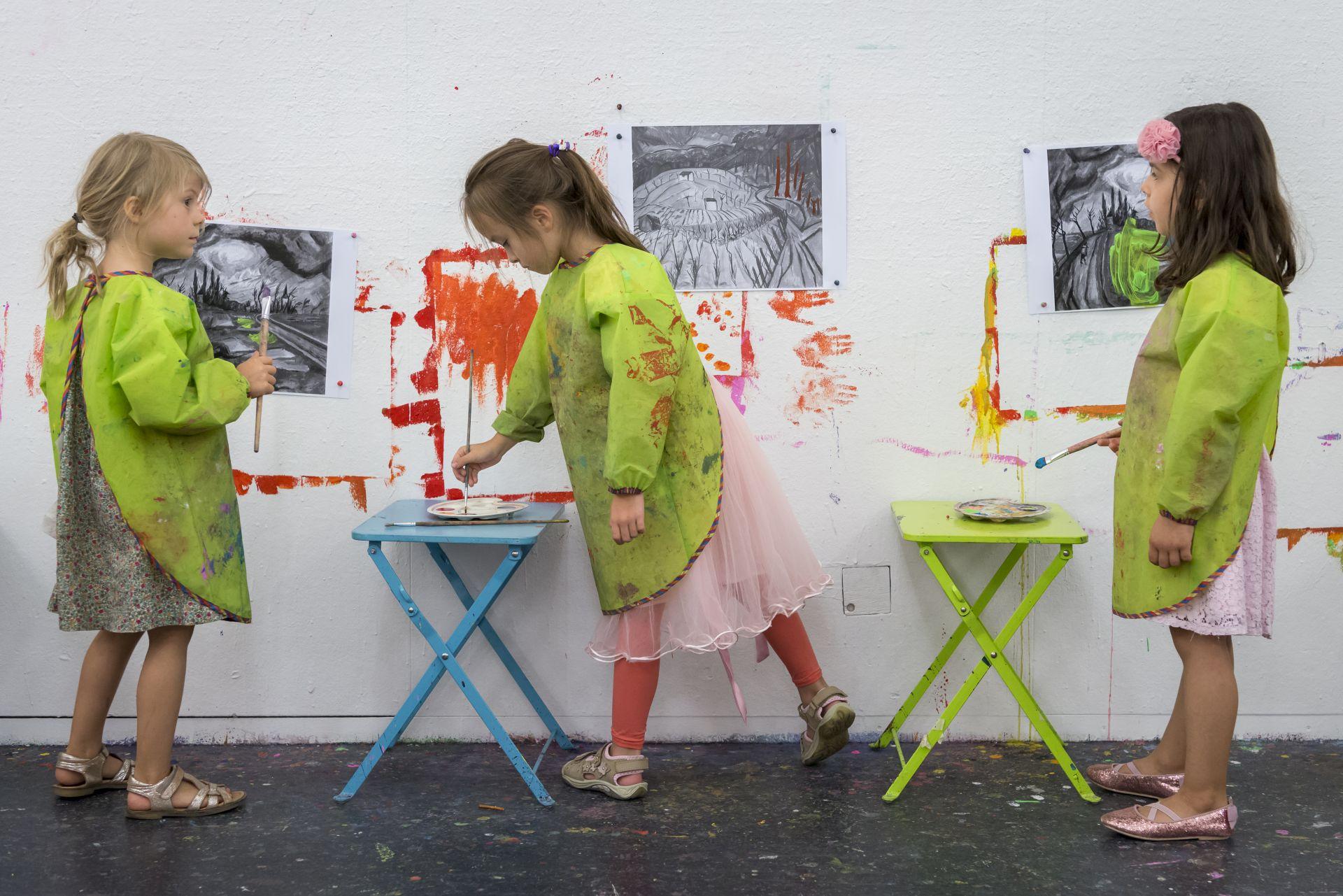 Drei Mädchen stehen in grünen Schürzen vor einer Wand und malen
