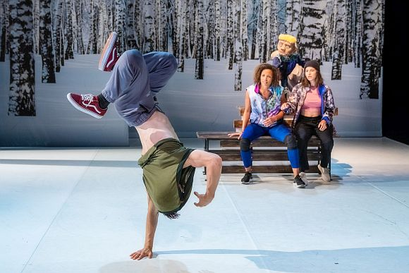 Breakdancer im Vordergrund, Schauspielerinnen und Puppe im Hintergrund auf einer Bank