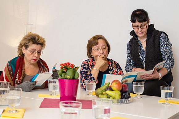 3 ältere Migrantinnen am Lesen einer Broschüre