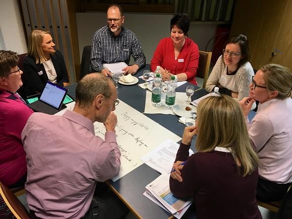 Gruppe am Tisch am Diskutieren