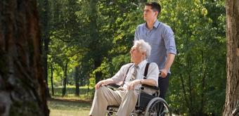 Junger Mann stösst älteren Mann im Rollstuhl vor sich her