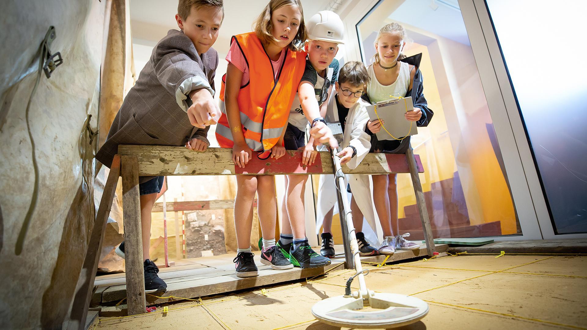 Mehrere Kinder suchen mit einem Metalldetektor einen Schatz.