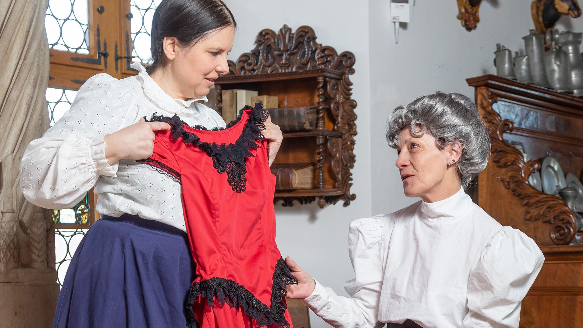 Theaterszene mit zwei historisch gekleideten Schauspielerinnen