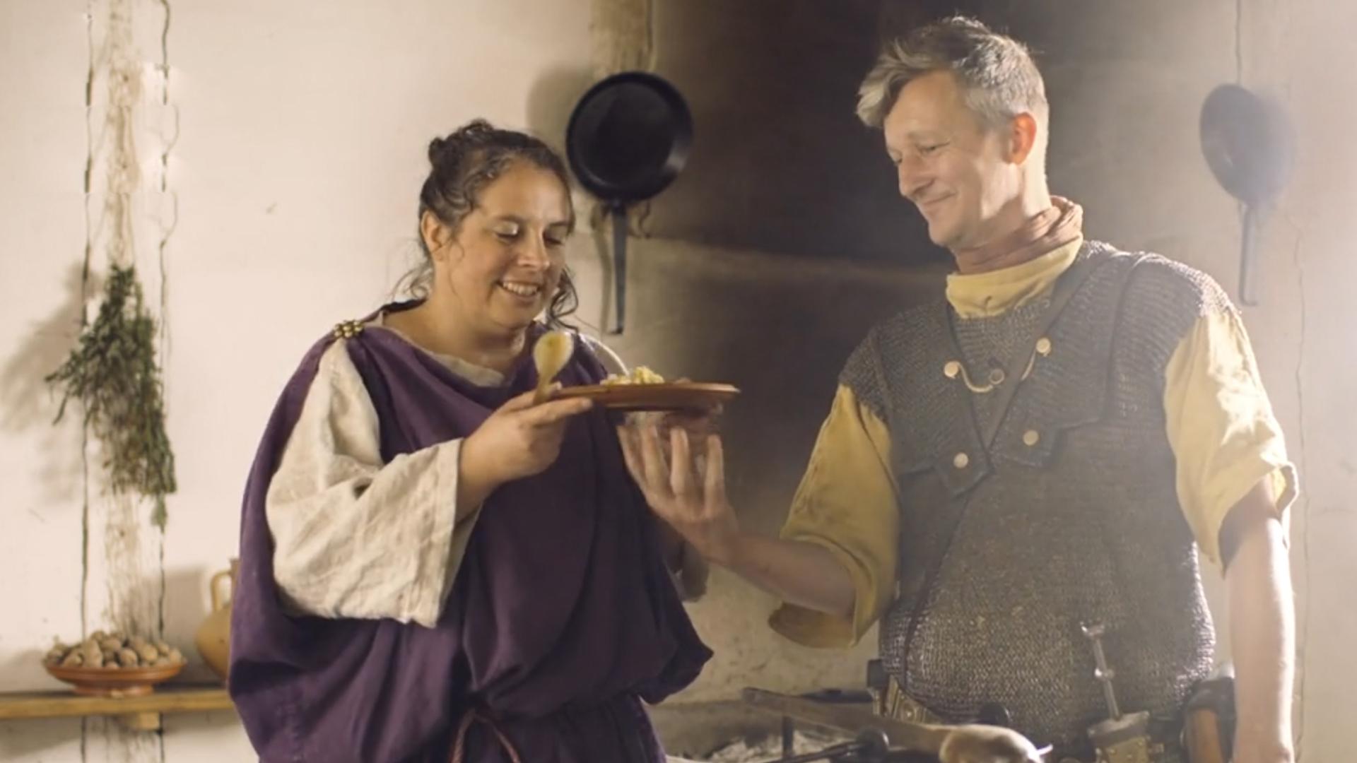 Legionär und Römerin stehen in einer antiken Küche