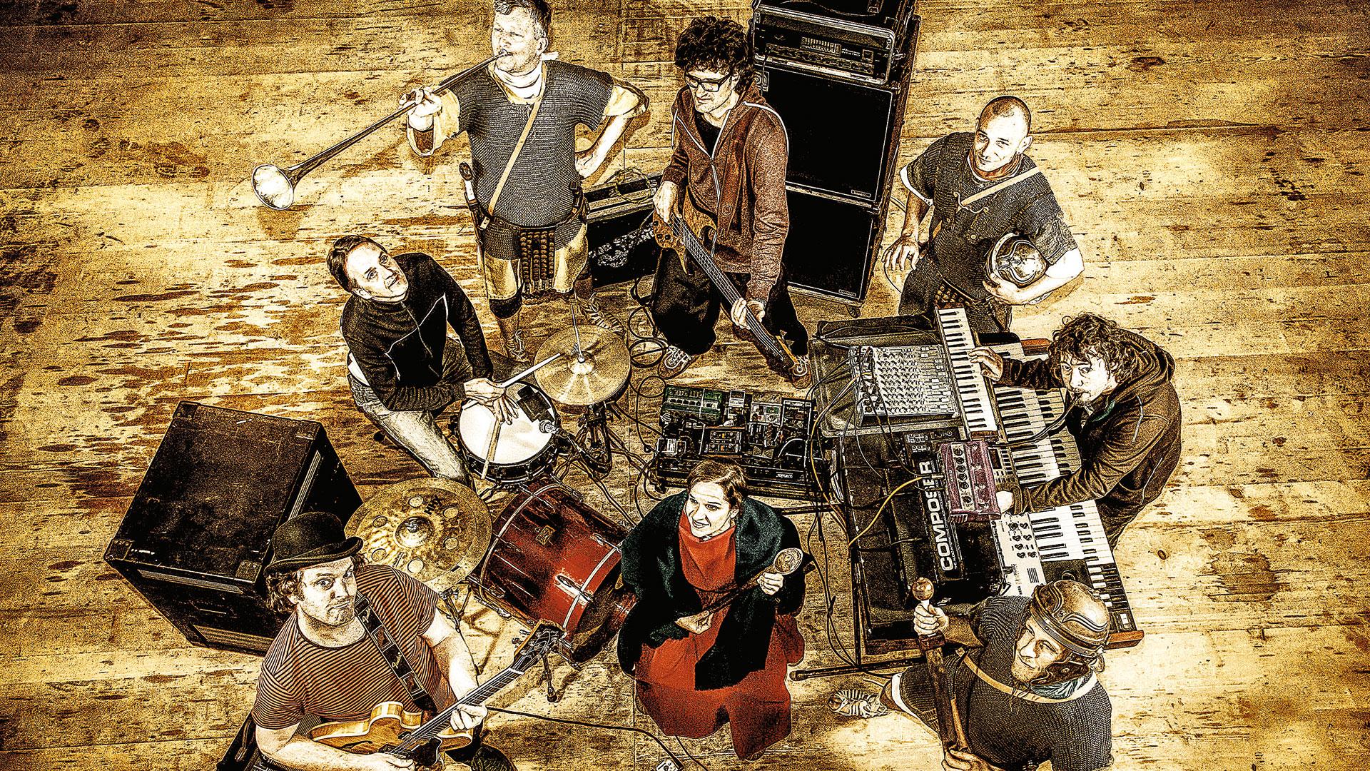 Römische gekleidete Männerund Frauen stehen inmitten einer Band inklusive Instrumenten.