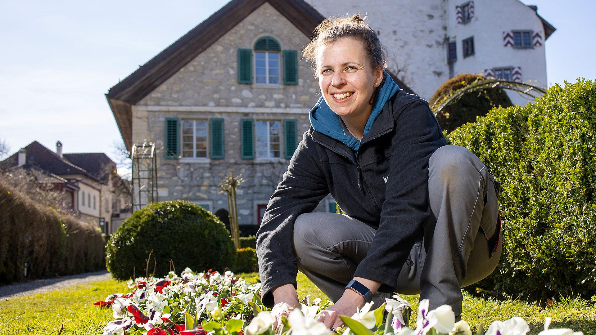 Eine Frau sitzt an einem blumenbeet, im Hintergrund Schloss Wildegg