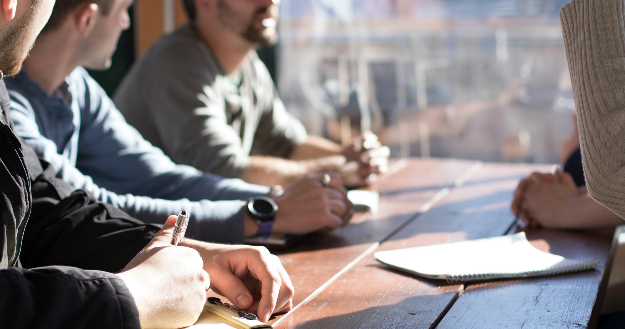 Eine Gruppe sitzt am Tisch und diskutiert
